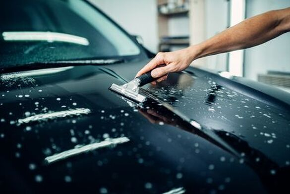 Picture of man's arm applying protective clear bra to hood of a car