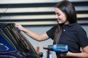Picture of woman tinting blue car with blue heat gun